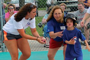 Volunteers encourage a Miracle League hitter