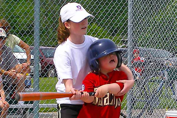 Batter swings with the help of a buddy